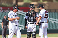 Salt River Rafters pitching coach Dave Burba (34), of the Colorado Rockies organization, meets with catcher Dom Miroglio (55), of the Arizona Diamondbacks organization, and relief pitcher Hector Lujan (35), of the Minnesota Twins organization, during an Arizona Fall League game against the Surprise Saguaros at Salt River Fields at Talking Stick on October 23, 2018 in Scottsdale, Arizona. Salt River defeated Surprise 7-5 . (Zachary Lucy/Four Seam Images)