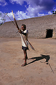 Koatinemo village, Brazil. Assurini Indian man demonstrating his bow and arrow skills outside the House of the Dead.