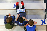 Laith Kook, 8, plays a game on his laptop in the gym while his classmates look on inside the Boys and Girls Club of Western Pennsylvania in the Lawrenceville neighborhood on Friday February 19, 2021 in Pittsburgh, Pennsylvania. (Photo by Jared Wickerham/Pittsburgh City Paper)