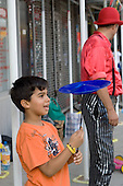 A young boy spins a plate at a circus skills workshop at Church Street Summer Festival 2005, Paddington, London.