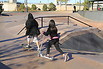 Boy on skateboard and girl riding a scooter at a park in Denver, Colorado. .  John offers private photo tours in Denver, Boulder and throughout Colorado. Year-round.