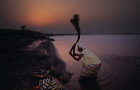 A man beats clothing while washing it in the Indus River on the bank at sunset.
