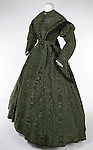 1978.24.1a-b <br /> Lady's Green Corded Silk Moire Dress. <br /> American Civil War<br /> Ca. 1864-1866.<br /> Silk moire, lace, and braided cord<br /> Gift of Mrs. Barton Harrington<br /> Also pictured is a Brooch [1983.55.10], ca. 1857, gold, enamel, and braided hair set under glass, gift of Mr. And Mrs. Mark Handwerk.<br /> Costume Collection<br /> Museum Department