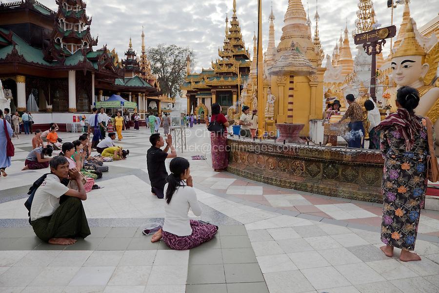 Myanmar, Burma.  Shwedagon Pagoda, Yangon, Rangoon.  Worshipers Praying in the Stupa Courtyard.