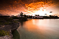 Sunrise seen from the western coast of Bermuda with small bungalows on the background