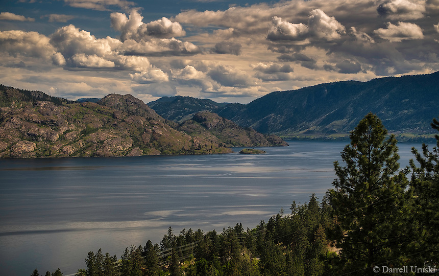 Fine Art Landscape print of Okanagan Lake near PeachLand in British Columbia Canada.<br /> <br /> This fine art print was captured during the spring season. The trees are very green, and the lake is a major source of water for the residents of the Okanagan Valley.<br /> <br /> Okanagan lake is a large lake that is 135 kilometres long, and during the spring season the clouds often move fairly rapidly down the valley. In this scene the low lying clouds were just passing over the mountain tops.