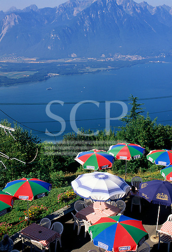 Caux, Switzerland. View from above of sunshades on the terrace of a restaurant; mountains and lake.