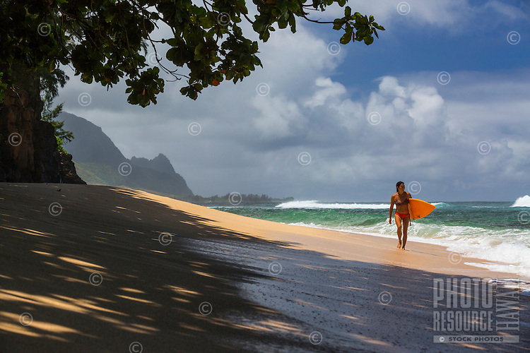 A woman walks down a beach with her surfboard on the north shore of Kaua'i, with Makana Mountain (a.k.a. Bali Hai) is in the distance.