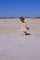 Girl wearing pink coat on beach<br />