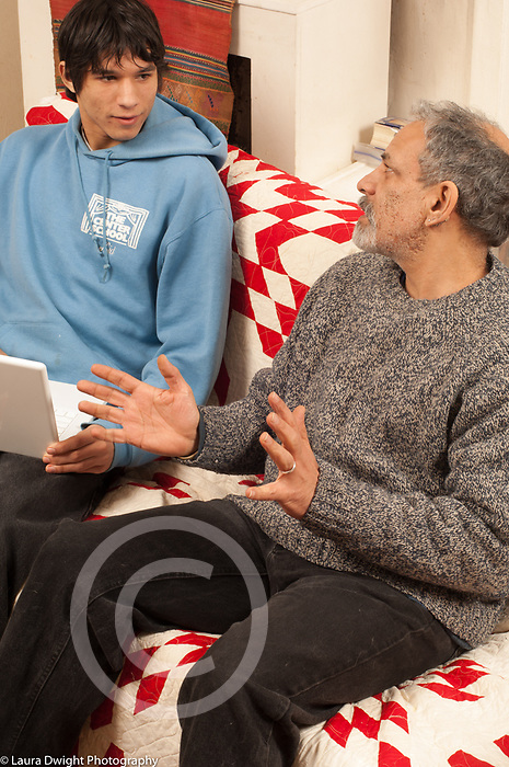 Teenage boy 16 years old sitting on couch with laptop argument or discussion with father