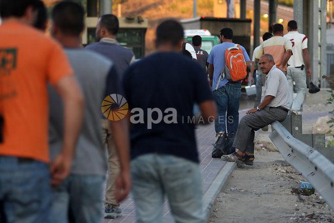 Palestinian workers wait to cross the Isreali controlled Modiin ( Bet seira )  checkpoint, between the West Bank and the Jewish settlement of Modiin Illit and all of Israeil , as they head to work in Israel and nearby settlements on October 7, 2010 . Photo by Eyad Jadallah