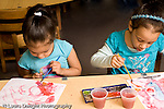Education Preschool 4-5 year olds art activity water color painting two girls painting side by side handedness one using left hand and the other using right hand horizontal