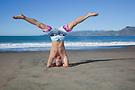 USA, California, San Francisco, portrait of man performing head stand on Baker Beach