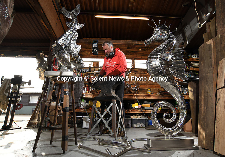 Pictured:  Sculptor Michael Turner working on his latest creations, using an anvil to hammer out metal.<br /> <br /> Metal sculptor Michael Turner has found enquires for his services have increased by 60% during the lockdown period as people have focus on improving their garden and interior spaces around the home.<br /> <br /> The sculptor who has been busy throughout lockdown from his Lymington workshop in the New Forest, Hampshire believes the increase could be down to those who are usually able to treat themselves by going out, but are now looking to spend their money on items to improve their lockdown experience and surroundings.<br /> <br /> © Simon Czapp/Solent News & Photo Agency<br /> UK +44 (0) 2380 458800