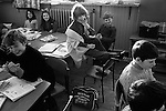 Junior school, schoolboys and schoolgirls in class, young disabled schoolgirl wearing callipers or leg The young girl is disabled she has braces - Caliper) on one leg and cant turn easily in her chair to see the teacher who is talking to the class, so she is allowed to sit on the table. The braces are just visible sitting on her shared desk. A Scotland for World Cup Munich 1974 schoolbag is on the floor. Breasclete Isle of Lewis and Harris,   Outer Hebrides, Scotland. 1974,