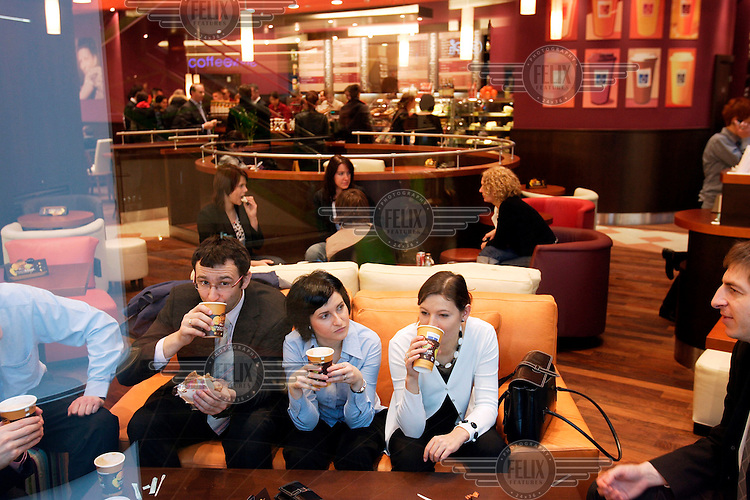Customers sip coffee at Coffee Heaven, a newly opened coffee shop at the Zlote Tarasy shopping centre in central Warsaw...