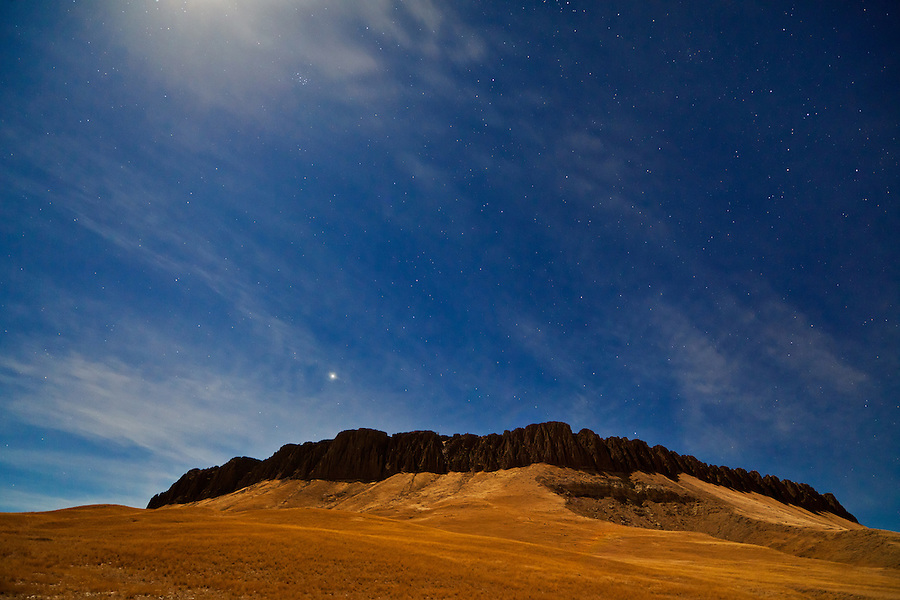 A full moon just out of the frame casts a swath of light onto Crown Butte, Montana, near Simms.