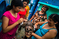 """Mayan women take care of a dried-up scull of a deceased family member during the bone cleansing ritual at the cemetery in Pomuch, Mexico, 26 October 2019. Every year on the Day of the Dead, people of Pomuch, a small Mayan community in the south of Mexico, visit the cemetery to take part in a pre-Hispanic tradition of cleaning of bones of their departed relatives (""""Limpia de huesos""""). People who die in Pomuch are firstly buried for three years in an above-ground tomb then the dried-up bodies are taken out, bones are separated, wrapped in a decorated cloth, put into a wooden crate, and placed on display among flowers for veneration."""