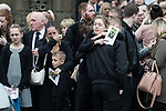 © Joel Goodman - 07973 332324 . 20/12/2017. Manchester, UK. Mourners hug and cry outside the church after the service . The funeral of 14-year-old Sam Berkley at Christ Church in Denton , East Manchester . Mourners wear red and white , the colours of Hattersley FC , for whom Berkley played . Amongst their number are pupils and friends from Audenshaw School . Berkley died after being hit by a grey BMW near junction 3 of the M67 in Hyde , East Manchester , on 1st December 2017 . Photo credit : Joel Goodman