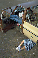 Humorous image of a woman doing truck repairs by the side of the road as a man sits and reads inside.