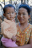 Myanmar, Burma.  Burmese Mother Holding Little Boy in a Village near Bagan.  The mother has traces of thanaka paste on her face, a cosmetic sunscreen.  Burman (Bamar) ethnic group.