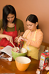 9 year old girl at home with mother in kitchen food preparation baking, stirring ingredients