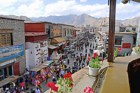 View of pilgrims circumambulating an alley of the Barkhor circuit in a clockwise direction around the Jokhang Temple during Saga Dawa festival, Lhasa, Tibet.