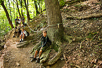 Boy Scouts attending Boy Scout resident camp at Camp Raven Knob in summer 2010 take a short rest while taking a hike. Camp Raven Knob Scout Reservation, one of the largest Boy Scout camps in the United States, is located within Boy Scouts of America's Old Hickory Council in Mt. Airy, North Carolina. Troops from across the US attend the camp's one-week residential boys' summer programs, which offer instruction on more than 40 merit badges, adventure programs and new Scout orientation.