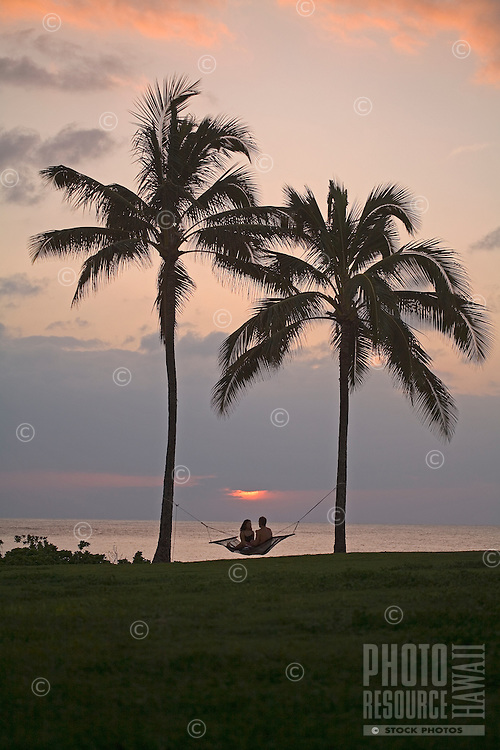 Couple relaxing in hammock at sunset under palm trees in front of the ocean, Haleiwa Alii Beach Park, North Shore of Oahu