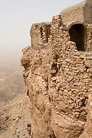 Tarmeisa, Libya - An Abandoned Berber Village in the Jebel Nafusa.  Originally from Byzantine times.  A strong wind from the south, the ghibli, stirs up dust in the air above the Sahel al-Jefara down below.