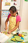 9 year old girl in kithen at home learning to cook cutting tomatillos with small knife cookbook open on table cooking with cactus beans tomatoes lemon