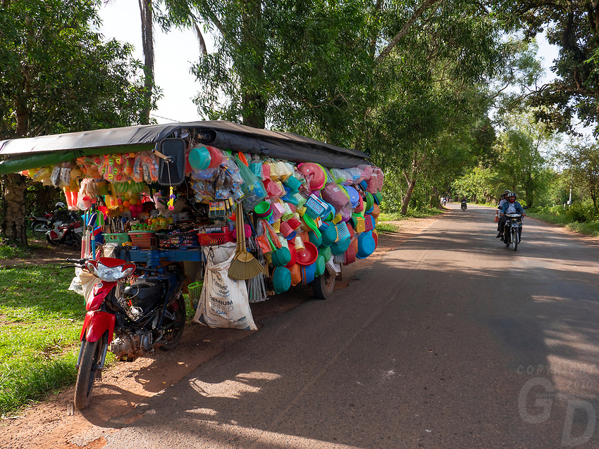 Country road outside Siem Reap and a fully loaded up Tuk Tuk with an enormous trailer carrying plastic household goods, Cambodia