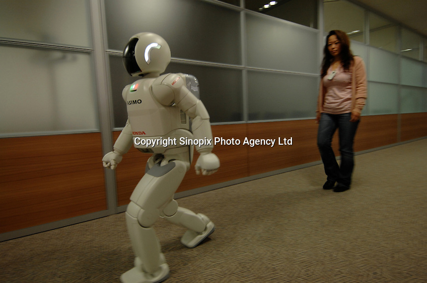 "The Asimo robot built by Honda in it's first test environment, the Honda headquarters in Tokyo where it lives in the office and performs simple tasks. Asimo is one of the most advanced humanoids in the world and is being developed as a ""home"" help robot."