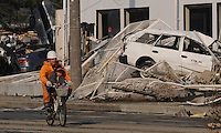 A rescue worker carries a child on a bike in front of devastation caused by the Japanese earthquake in Sendai, Japan. One of the biggest earthquakes ever recorded struck off the coast of Japan on 11 Mar 2011 had killed thousands of people. The death toll was expected to rise dramatically, with tens of thousands reported missing..13 Mar 2011.....