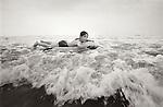 1978. Brigantine beach, NJ. Kirsten riding on float in the surf.
