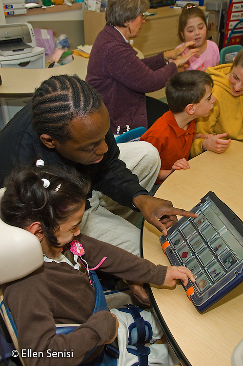 MR / Albany, NY.Langan School at Center for Disability Services .Ungraded private school which serves individuals with multiple disabilities.Teaching assistant (African-American) help a student use an alternative and augmentative communication device during speech and language development lesson. Girl: 7, cerebral palsy, nonverbal with expressive and receptive language delays. In the background teachers work with other special needs students..MR: Wes2, Del16.© Ellen B. Senisi