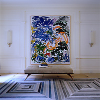 The white panelled entrance hall is given a shot of pattern and colour with a painting by Joan Mitchell and a rug by Diamond Baratta Design