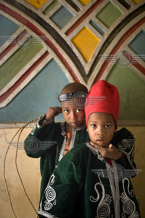 Two young boys in their best robes prepare for the  Kano Durbar. This spectactular parade of horsemen, musicians and people celebrates the Muslim festival of Eid al-Adha and is the time for the populace to pledge their loyalty to their traditional ruler, the Emir of Kano.