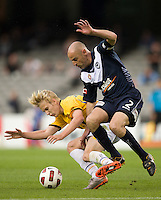 MELBOURNE, AUSTRALIA - NOVEMBER 06: Kevin Muscat of the Victory is challenged by Bas van den Brink of Gold Coast United during the round 13 A-League match between the Melbourne Victory and Gold Coast United at Etihad Stadium on November 6, 2010 in Melbourne, Australia (Photo by Sydney Low / Asterisk Images)