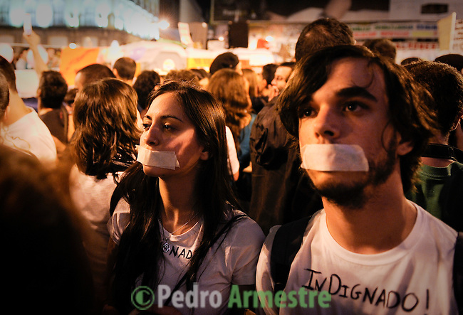 people cover their mouths in protest at the Puerta del Sol square in Madrid on May 21, 2011 during a protest against Spain's economic crisis and its sky-high jobless rate. Young people camped in main squares across Spain in the largest spontaneous protests since the country plunged into recession after the collapse of a property bubble in 2008. (c) PEDRO ARMESTRE