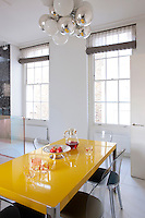 """A bright yellow lacquer table and Murano """"Vanity"""" chairs in the breakfast area are situated beneath a pendant light by Emmanuel Babled in this light kitchen"""