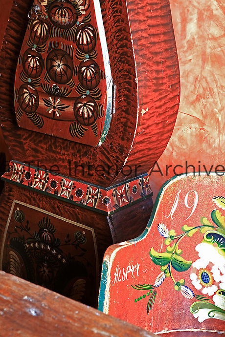 Detail of the hand-painted decoration on an antique Mora clock and a wooden chair