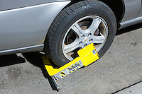 A Paylock tire boot immobilizes a car with outstanding parking violations in New York City.