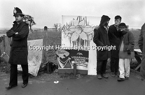 Greenham Common Women's Peace Camp 1985. Peaceful protesting hanging around in the winter cold monitored by a loan policeman.