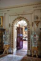 Two large Oriental inspired vases flank a gilt edged doorway into another reception room
