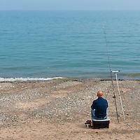 Man fishing on Ramsey Beach, Isle of Man.