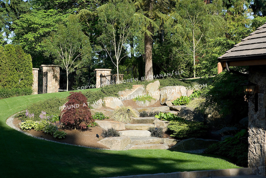 large flat stone steps and carefully placed landscape rocks boulders help tame this steep grade change in the lawn of an estate sized property that leads to the lower level garage