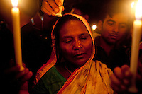 Relatives of the victims of the Rana Plaza building collapse hold lit candles as they gather to pay tributes at the venue of the tragedy at Savar, outskirts of Dhaka, Bangladesh