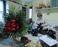 Florist Connie Bailey in Buckhannon, WV, makes black ribbon bows Friday, Jan. 6, 2006, to be displayed to honor the miners killed in a mine explosion Monday at a mine in Sago. Twelve miners died in the explosion. (Photo by Gary Gardiner)..<br />