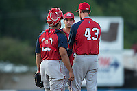Hagerstown Suns relief pitcher Robert Orlan (26) and catcher Raudy Read (29) listen to pitching coach Sam Narron (43) during the game against the Kannapolis Intimidators at Intimidators Stadium on July 18, 2015 in Kannapolis, North Carolina.  The Intimidators defeated the Suns 1-0.  (Brian Westerholt/Four Seam Images)